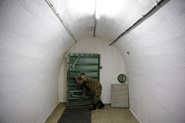 A member of the armed forces of Bosnia and Herzegovina opens a door at Tito's underground secret bunker (ARK) in Konjic, October 16, 2014. In the early 1950s, Josip Broz Tito, the late leader of the former Yugoslavia, ordered the building of the secret bunker, located 900 feet (270 m) underground and near the Bosnian town of Konjic, to safeguard the country's ruling class in case of a nuclear attack. Construction at the complex, which had a cost equivalent price tag of $4.6 billion, continued until 1979, the year before Tito died. (Photo by Dado Ruvic/Reuters)