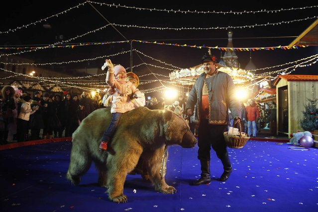 An artiste leads a bear as a child sits on it during the first day of a fair organized by GUM departmental store for the upcoming Christmas and New Year celebrations at Moscow's Red Square, November 29, 2014. (Photo by Maxim Zmeyev/Reuters)