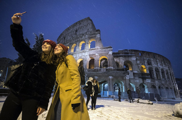 Two women take a selfie in front of the ancient Colosseum during a snowfall, early Monday, February 26, 2018. Romans have awoken to a rare snowfall, after an Arctic storm passing over much of Europe dumped enough snow to force schools to close and public transport to reduce services. (Photo by Angelo Carconi/ANSA via AP Photo)