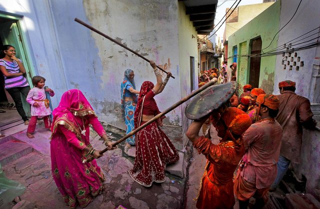Woman from the village of Barsana hit villagers from Nandgaon with wooden sticks during the Lathmar Holy festival, on March 21, 2013. (Photo by Manish Swarup/Associated Press)