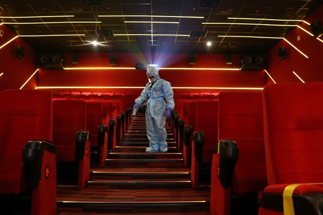 A worker wearing personal protective equipment (PPE) sanitizes seats inside the Inox Leisure movie theatre ahead of its reopening, amidst the outbreak of the coronavirus disease (COVID-19), in Mumbai, India, October 13, 2020. (Photo by Niharika Kulkarni/Reuters)
