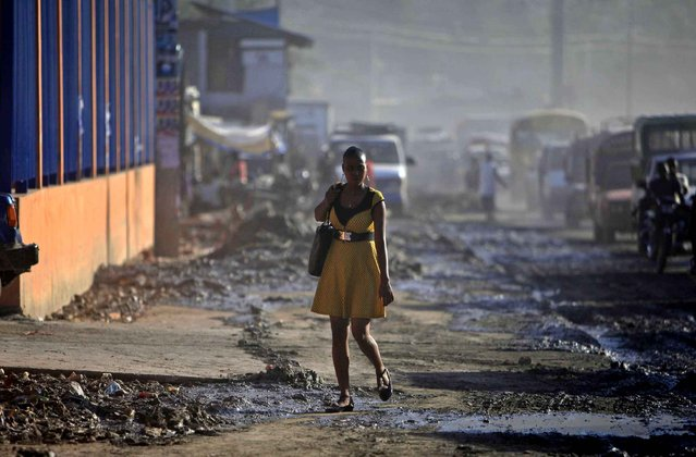 A woman in a dress walks on a mud covered sidewalk in Port-au-Prince, Haiti, Wednesday, October 28, 2015. (Photo by Ricardo Arduengo/AP Photo)