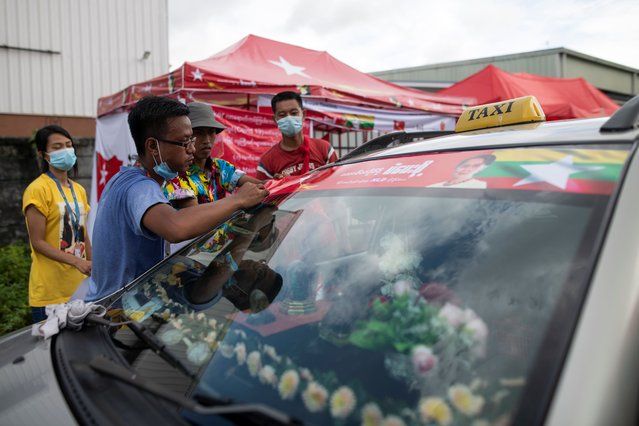 A volunteer puts a sticker of Myanmar State Counselor Aung San Suu Kyi on a car bonnet in Yangon, Myanmar on September 12, 2020. Myanmar will hold its general election on November 8. (Photo by Shwe Paw Mya Tin/NurPhoto via Getty Images)