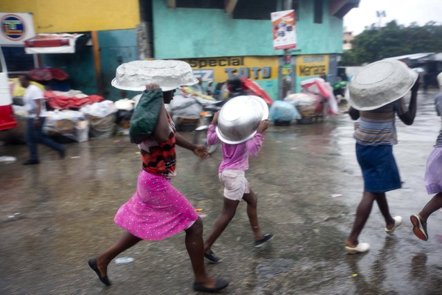 Women cover their heads with pans as they walk in a light rain brought by Hurricane Matthew in Port-au-Prince, Haiti, Tuesday, October 4, 2016. (Photo by Dieu Nalio Chery/AP Photo)