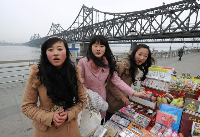Chinese tourists buy North Korean souvenirs beside the Yalu River Bridge leading to North Korea during the funeral of the late leader Kim Jong Il, at the Chinese border town of Dandong on December 28, 2011. (Photo by Mark Ralston/AFP Photo)