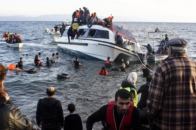 Volunteers and local residents help refugees and migrants disembark from a small vessel after their arrival in Skala Sykaminias on the northeastern Greek island of Lesbos on Friday, October 30, 2015. Greek authorities say 21 people have died in other islands after two boats carrying migrants and refugees from Turkey to Greece sank overnight, in the latest deadly incidents in the eastern Aegean Sea. (Photo by Kostis Ntantamis/AP Photo)