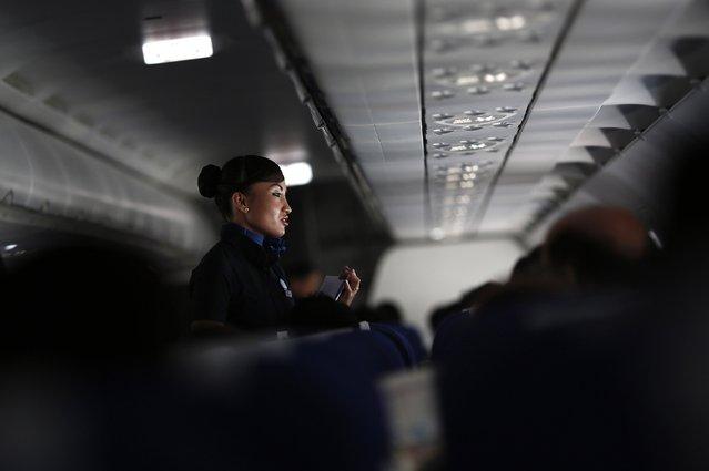 An Indigo Airlines' flight attendant talks with a traveller during a flight from New Delhi to Srinagar city November 21, 2014. Picture taken November 21, 2014. (Photo by Adnan Abidi/Reuters)