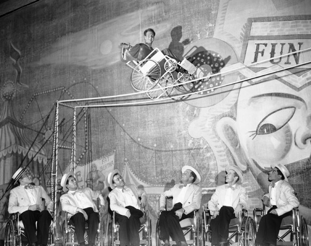 """Eddie Teal, 24-year-old paraplegic from Oakland, Calif., practices his """"tight rope"""" balancing act during rehearsal for the stage production of  """"It's a Great Day"""" at Blackstone Theater in Chicago, Ill.,  February 7, 1951.  Eddie is one of 20 wheel chair vets in the cast of the musicals review which got its start nearly two years earlier at the Birmingham Veteran's hospital in Van Nuys, Calif, The Group raised $500.00 in 31 benefit performances for the March of Dimes and is now bidding for professional recognition. (Photo by Ed Maloney/AP Photo)"""
