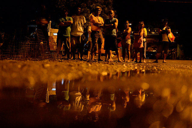 """Residents are reflected in a pool of water as they look at two bodies (not pictured) lying on a sidewalk,  who police said were killed after a drug """"Shabu"""" (Methamphetamine Chloride) buy-bust operation in Quezon city, Metro Manila, Philippines, October 9, 2016. (Photo by Ezra Acayan/Reuters)"""