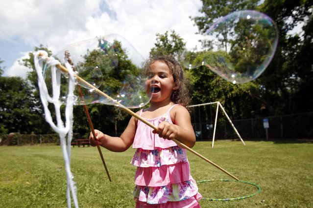 Ellana Kruger, 3, gets excited about making big bubbles at the 2015 Gather-In at Pitt Park in Pittsfield, Mass., Saturday, July 25, 2015. (Photo by Stephanie Zollshan/The Berkshire Eagle via AP Photo)