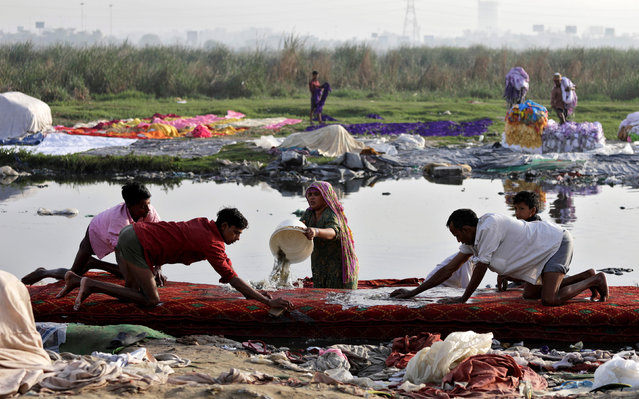 People wash clothes on the banks of the river Yamuna in New Delhi, India, March 15, 2018. (Photo by Saumya Khandelwal/Reuters)