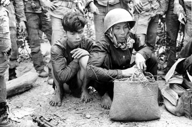 Viet Cong guerrilla fighters, captured by Vietnamese Marines in battle near Long Binh on the Mekong Delta, crouch on the ground with their hands tied during the Vietnam War, February 27, 1964. One wears a U.S. type protective helmet which he was wearing when he was captured. (Photo by Horst Faas/AP Photo)