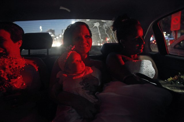 A bride (C) from Santa Marta slum holds her baby inside a police car accompanied by other brides, on their way to their group wedding in Rio de Janeiro December 17, 2014. (Photo by Pilar Olivares/Reuters)