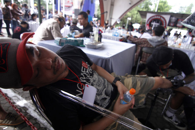 A man fall a sleep as he gets a tattoo on his leg during Bandung Body Art Festival at in Bandung, West Java, on December 7, 2014. (Photo by Rezza Estily/JG Photo)