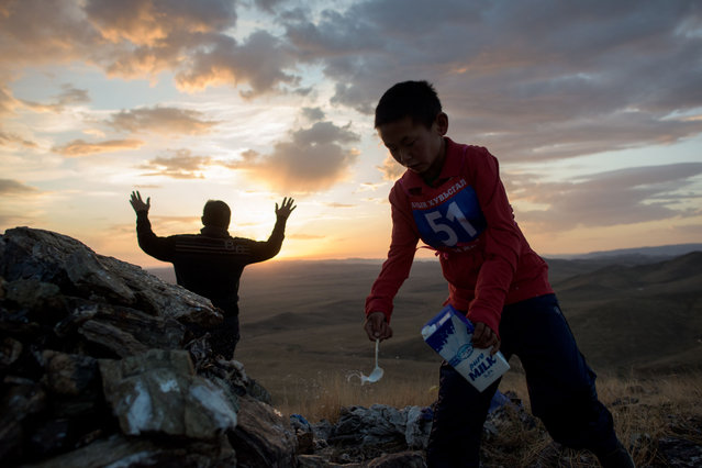 "This picture taken on July 10, 2015 shows 13-year-old jockey Purevsurengiin Togtokhsuren (R) attending a 'tsatsal urgukh' (giving milk to the gods) ceremony next to his coach during sunrise, on a hill close to his ""yurt"" in Khui Doloon Khudag, some 50 kms west of Ulan Bator. (Photo by Johannes Eisele/AFP Photo)"
