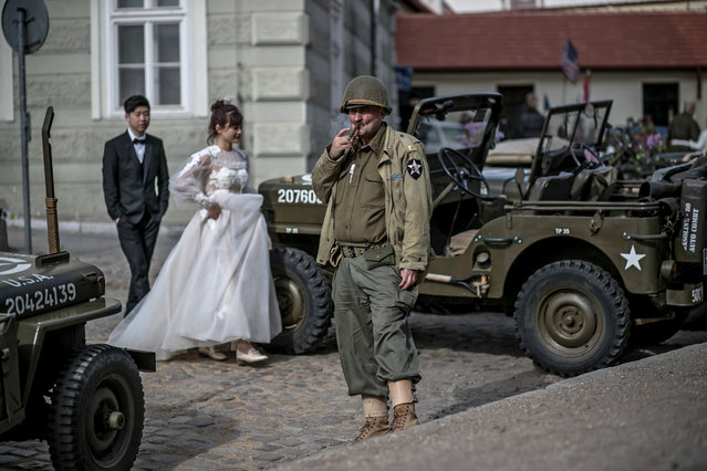 """A history enthusiast (C) dressed in US Army uniform from World War II smokes a cigarette during the """"Convoy of Liberty"""" in Prague, Czech Republic, 27 April 2018. The """"Convoy of Liberty"""" commemorates the liberation of the western part of Czech Republic from Nazi oppression by the US Army at the end of the World War II in APril and May 1945. The convoy's route begins on the bank of Vltava river in Prague and traditionally makes its first stop in front of the US Embassy, where it is welcomed by a Czech Army Military Band and many spectators. (Photo by Martin Divisek/EPA/EFE)"""