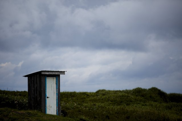 A toilet stands in a field on private property in the town of Yuzhno-Kurilsk on Kunashir Island which is part of the Kuril Islands group in Russia, September 16, 2015. (Photo by Thomas Peter/Reuters)