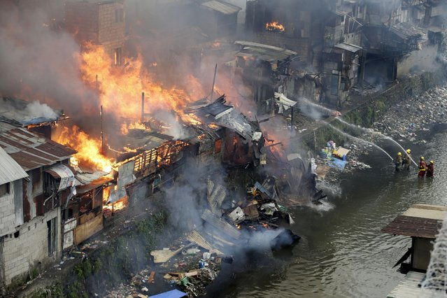 Firefighters fight the fire at shanties from a creek in suburban Quezon city, north of Manila, Philippines during an early morning fire Thursday, January 1, 2015. (Photo by Bullit Marquez/AP Photo)