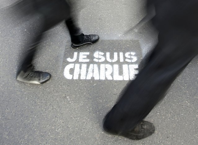 """People walk past a grafitti tag reading """"I am Charlie"""" as they take part in a solidarity march (Marche Republicaine) in the streets of Paris January 11, 2015. (Photo by Eric Gaillard/Reuters)"""