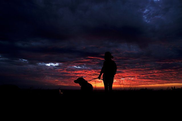 A woman wearing a face mask walks with her pet dog at sunset, during the coronavirus disease (COVID-19) outbreak as the number of daily infections reached a record, in Mellieha, Malta on January 9, 2021. (Photo by Darrin Zammit Lupi/Reuters)