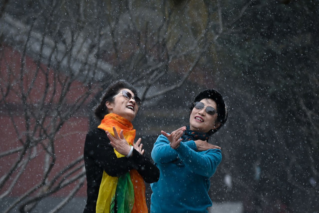 Two women dance at a park on a snowy day in Beijing on January 25, 2021. (Photo by Wang Zhao/AFP Photo)