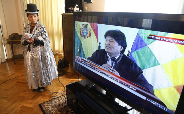An indigneous Aymara reporter looks at a TV screen showing a live image of Bolivia's President Evo Morales giving a press conference at the presidential residence in La Paz, Bolivia, Monday, January 19, 2015. After championing Bolivia's 36 indigenous groups and enshrining their rights in the 2009 constitution, Morales alienated lowlands natives by promoting a highway through a nature reserve. (Photo by Juan Karita/AP Photo)