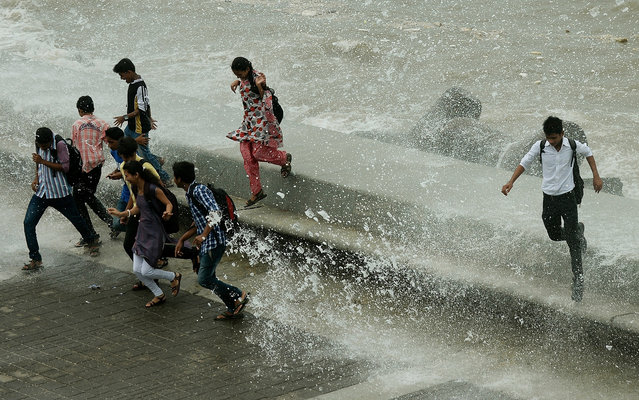 Indian pedestrians run from water splashing over a sea wall in Mumbai on June 24, 2013. The monsoon, which covers the subcontinent from June to September, usually brings some flooding. But the heavy rains arrived early this year, catching many by surprise and exposing a lack of preparedness. (Photo by Punit Paranjpe/AFP Photo)