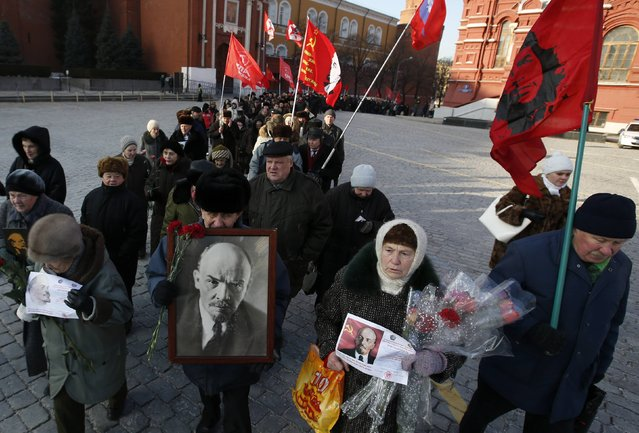 Communist supporters hold flags and portraits of Soviet State founder Vladimir Lenin during a wreath laying ceremony at the Lenin's mausoleum on Moscow's Red Square January 21, 2015. Communists gathered on Wednesday to commemorate the 91st death anniversary of Vladimir Lenin. (Photo by Sergei Karpukhin/Reuters)
