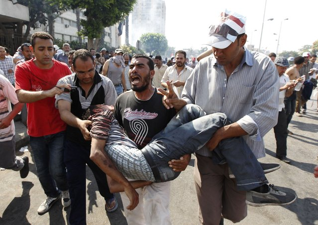 Protesters who support former Egyptian President Mohamed Mursi carry an injured man during clashes outside the Republican Guard building in Cairo July 5, 2013. (Photo by Louafi Larbi/Reuters)
