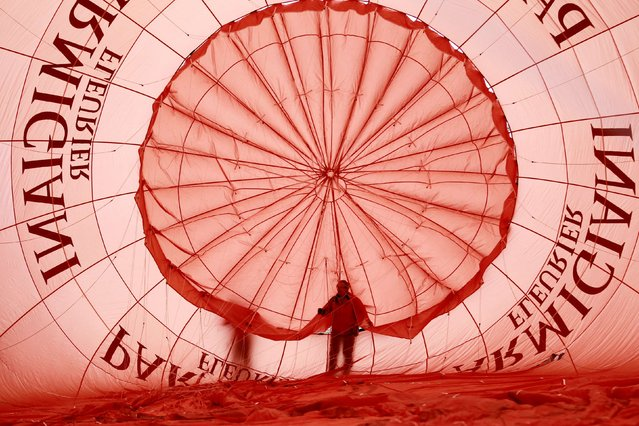 A pilot checks his balloon before the 37th International Hot Air Balloon Week in Chateau-d'Oex, January 24, 2015. (Photo by Pierre Albouy/Reuters)