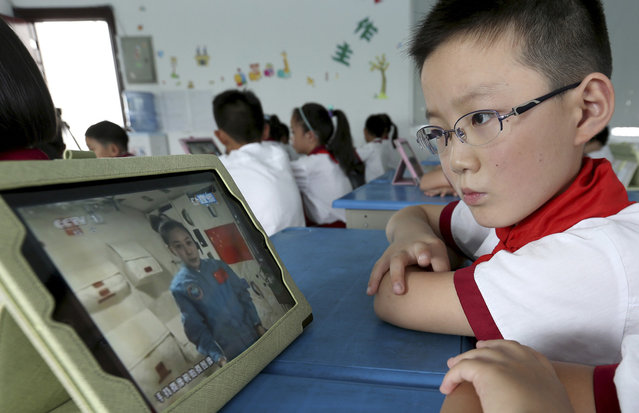 A student looks at an iPad as his class watches a live broadcast of a lecture given by Shenzhou-10 spacecraft astronauts on the Tiangong-1 space module, at a primary school in Quzhou, Zhejiang province, on June 20, 2013. (Photo by Reuters/Stringer via The Atlantic)