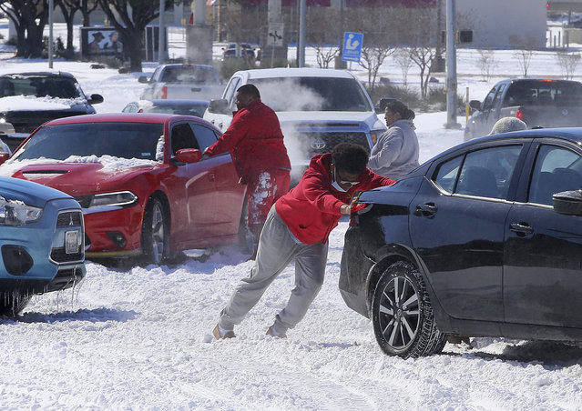 People push a car free after spinning out in the snow Monday, February 15, 2021 in Waco, Texas. A winter storm that brought snow, ice and plunging temperatures across the southern Plains and caused a power emergency in Texas stretched its frigid fingers down to the Gulf Coast. (Photo by Jerry Larson/Waco Tribune-Herald via AP Photo)