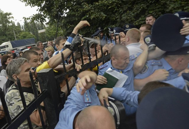 A protester uses teargas against police officers as angry residents attempt to storm the local police station in Kiev July 12, 2013. People angered by the beating of a local woman in which they said police officer was involved, attacked a police headquarters, local media reported. (Photo by Reuters/Stringer)