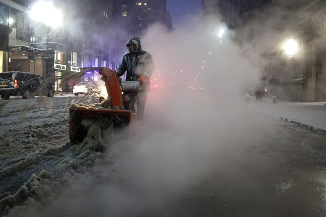 A worker pushes a snow blower down Lexington Avenue near Grand Central Terminal as it snows in the Manhattan borough of New York January 26, 2015. (Photo by Carlo Allegri/Reuters)