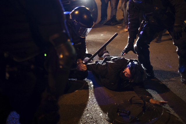 A demonstrator is detained by police during clashes following a protest condemning the arrest of rap singer Pablo Hasél in Barcelona, Spain, Saturday, February 27, 2021. (Photo by Felipe Dana/AP Photo)