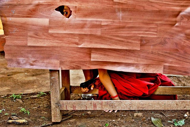 A novice Tibetan Buddhist monk peeps through a hole as he hides behind a desk holding a toy gun during a break from their spiritual leader the Dalai Lama's religious sermon outside the Gyudmed Tantric Monastery southwest of Bangalore, India, on July 15, 2013. (Photo by Aijaz Rahi/Associated Press)