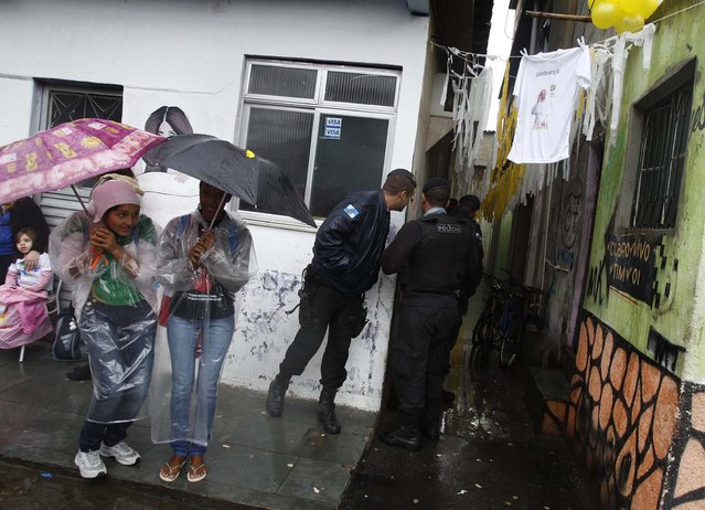 Residents of the Varginha slum wait under umbrellas, while police guard the street, as they wait for Pope Francis to visit the slum on July 25, 2013. (Photo by Pilar Olivares/Associated Press)