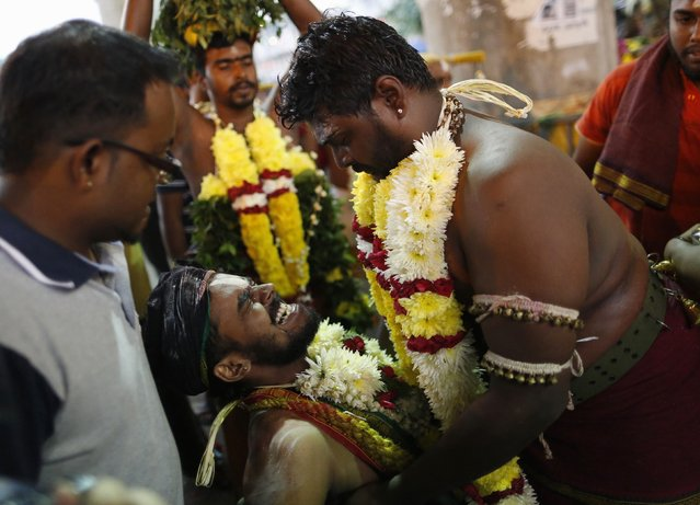 A Hindu devotee reacts after his cheek is pierced before starting his pilgrimage to the Batu Caves temple during Thaipusam in Kuala Lumpur February 2, 2015. (Photo by Olivia Harris/Reuters)