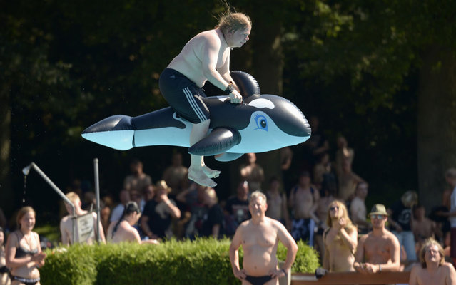 A Heavy Metal fan, sitting on a plastic whale float, jumps into a swimming pool during the 24th Wacken Open Air Festival in Wacken, August 2, 2013. More than 75,000 heavy metal fans are expected to attend the largest heavy metal festival in the world, organizers said. (Photo by Fabian Bimmer/Reuters)