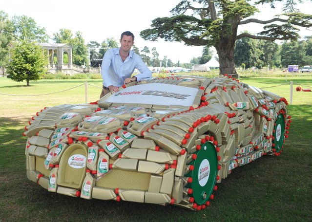 Lord Pembroke, co-founder of Wilton Classic and Supercars (WCS), with a one-off, life-sized replica of a Bugatti Veyron made from over 400 Castrol EDGE bottles and barrels, at Wilton House in Salisbury, on August 4, 2013. (Photo by Barry Batchelor/PA Wire)
