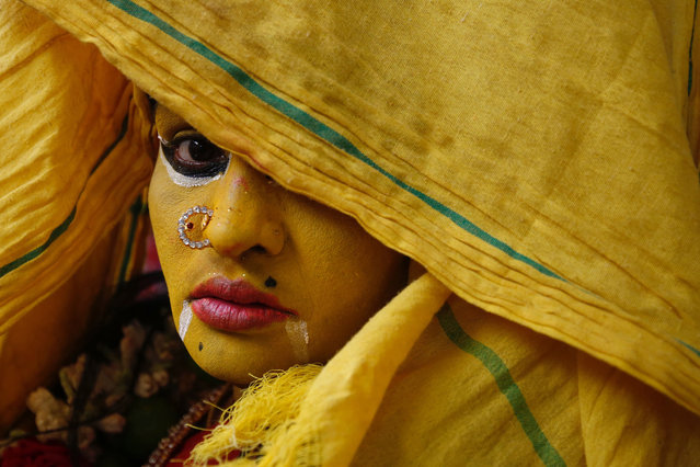 "A woman dressed in the style of a Hindu goddess keeps her face partially covered for a ritual during Maha Shivaratri celebrations on March 12, 2021 in Kaveripattinam, India. Maha Shivaratri is a major Hindu festival celebrated annually in honour of the god, Shiva. The festival is observed with chanting prayers, fasting, and meditating to overcome ""darkness and ignorance"" in life. (Photo by Abhishek Chinnappa/Getty Images)"