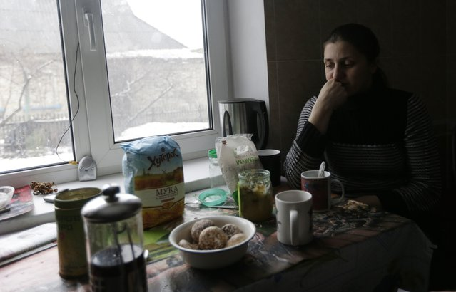 In this picture taken, Monday, February 9, 2015, Sveta Banina sits in her kitchen in Donetsk. Day and night, mortars and rockets rain down on the rebel stronghold in eastern Ukraine – mainly in the city's outlying districts, where the poorest people live. (Photo by Petr David Josek/AP Photo)