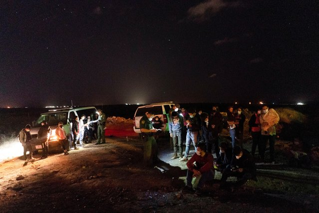 Asylum-seeking migrants' families wait to be transported by the U.S. Border Patrols after crossing the Rio Grande river into the United States from Mexico in Roma, Texas, U.S. April 5, 2021. (Photo by Go Nakamura/Reuters)