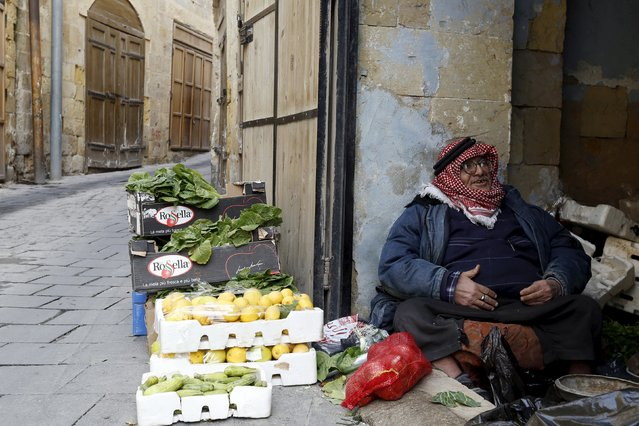A vegetable seller waits for customers in his shop at the Hammam Street Market, on one of the oldest commercial streets in Salt, Jordan, January 5, 2016. (Photo by Muhammad Hamed/Reuters)