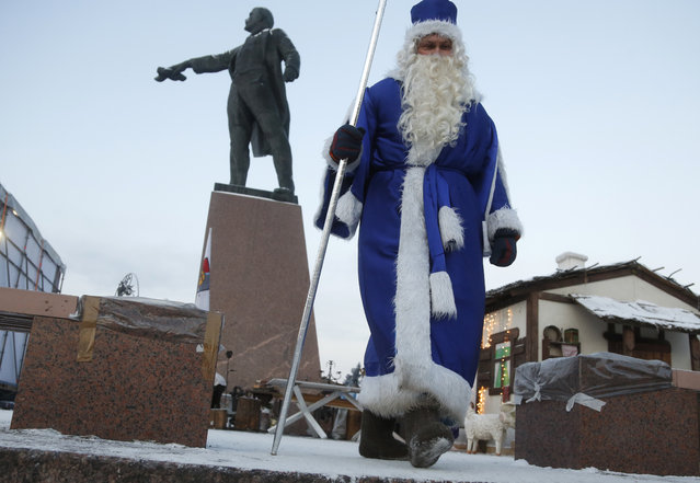 An actor dressed as Grandfather Frost, the Russian Santa Claus, walks next to a statue of Soviet Union founder Vladimir Lenin during celebration of Orthodox Christmas in St.Petersburg, Russia, Thursday, January 7, 2016. (Photo by Dmitry Lovetsky/AP Photo)