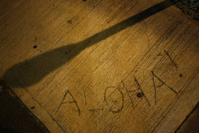 The shadow of a parking meter falls across the word aloha - the traditional Hawaiian word of greeting - etched in a city sidewalk in Honolulu, Hawaii December 22, 2015. (Photo by Jonathan Ernst/Reuters)
