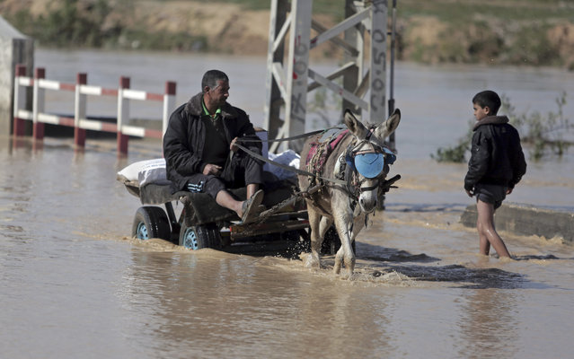 A Palestinian man carries goods on a donkey cart through a muddy, rain flooded street in the Bedouin village of al-Moghraka, central Gaza Strip, Sunday, February 22, 2015. (Photoby Khalil Hamra/AP Photo)