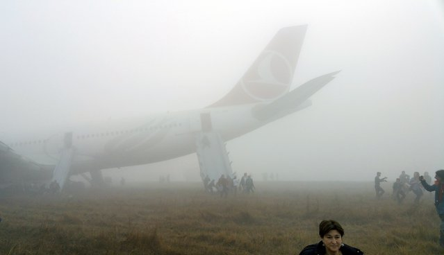 Passengers exit from a Turkish Airlines plane soon after it overshot from the runway in Kathmandu March 4, 2015. According to local media, all passengers and crew members of the flight were rescued. REUTERS/Dikesh Malhotra