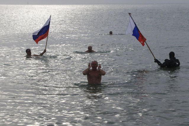 People hold Russian national flags as they swim in cold waters of the Black Sea during Orthodox Epiphany celebrations in the port city of Yevpatoriya, Crimea, January 19, 2016. (Photo by Pavel Rebrov/Reuters)