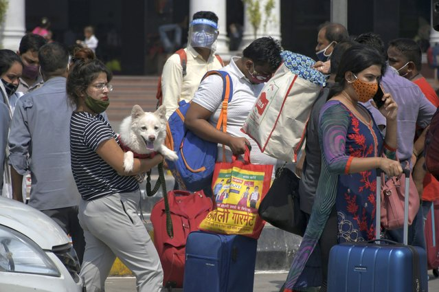 Passengers walk outside the New Delhi railway station in New Delhi, India, Monday, June 7, 2021. Businesses in two of India's largest cities are reopening as part of a phased easing of lockdown measures in several states now that the number of new coronavirus infections in the country is on a steady decline. (Photo by Ishant Chauhan/AP Photo)